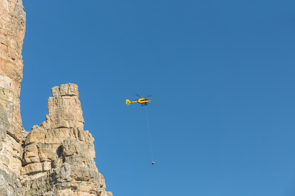 Yellow helicopter carrying loads in the Dolomites