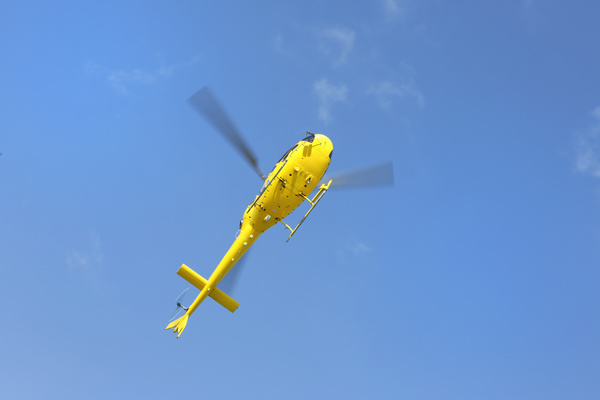 Yellow helicopter flying under blue sky Stock Photo 01