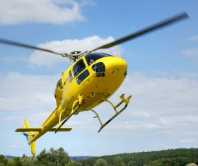 Yellow helicopter flying under blue sky Stock Photo 02