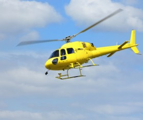 Yellow helicopter flying under blue sky Stock Photo 03