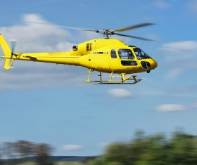 Yellow helicopter flying under blue sky Stock Photo 04