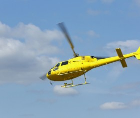 Yellow helicopter flying under blue sky Stock Photo 05