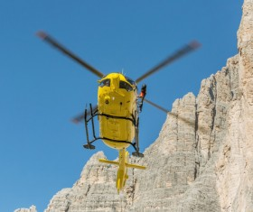 Yellow helicopters walk through the dolomite Stock Photo