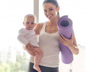Young mother holding the baby holding a yoga mat Stock Photo