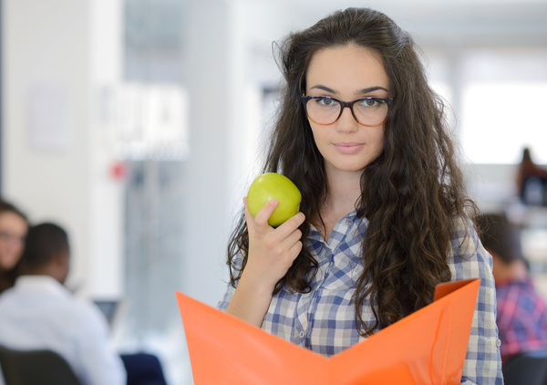 Young woman holding fruit and folder