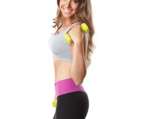 Young women with dumbbells doing arm movement