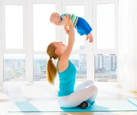 Bright living room Young mother holding a baby Stock Photo