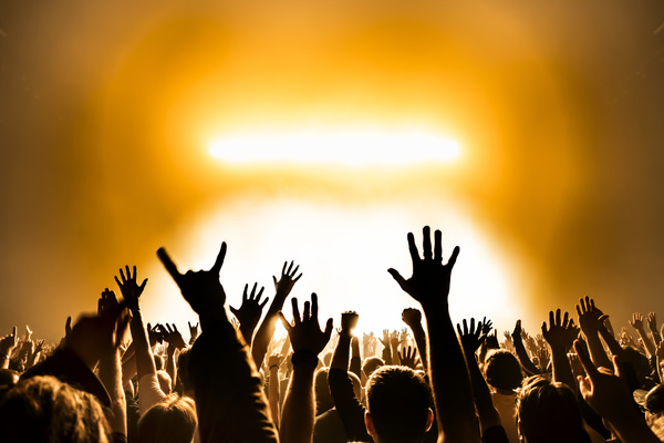 Cheering crowd of rock concerts with stage fireworks