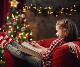 Christmas girl sitting on the sofa drawing Stock Photo