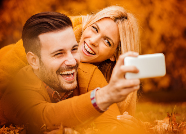 Happy couple taking photos on cell phone Stock Photo free download