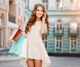 Happy young woman having shopping bags to call