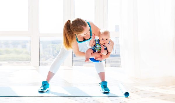 Holding the baby doing yoga young mother Stock Photo
