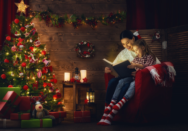 Mother and daughter sitting on the couch reading Christmas Eve