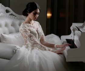 Sitting in front of the piano white wedding young charming bride