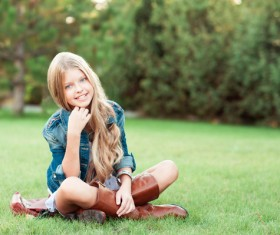 Sitting on a park grass blonde little girl
