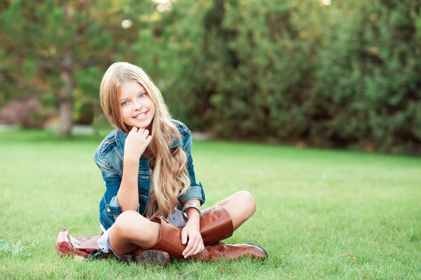 Sitting on a park grass blonde little girl