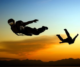 Sunset and skydiving athletes Stock Photo