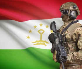 Flag of the Republic of Tajikistan and heavily armed soldiers