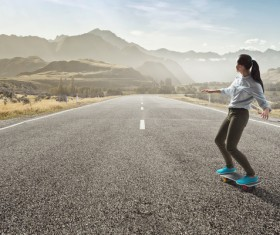 Girl playing skateboard on the highway HD picture