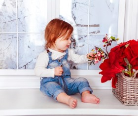 Pretty baby on the windowsill with flower baskets