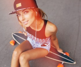 Sitting on the skateboard listening to music girl HD picture