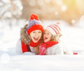 Smiling mother and daughter lying in the snow Stock Photo