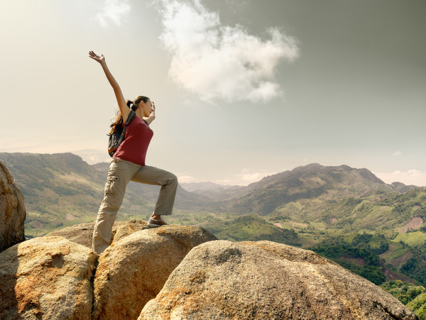 Standing woman cheering on high rocks HD picture