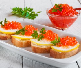 Bread red caviar with lemon and a bowl of red caviar