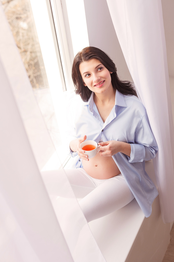 Pregnant women drinking coffee on the windowsill Stock Photo