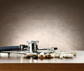Stethoscope on tabletop and pill Stock Photo