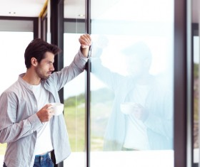 The handsome man drinking coffee in the window Stock Photo