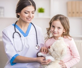 A little girl playing with a pediatrician Stock Photo 01