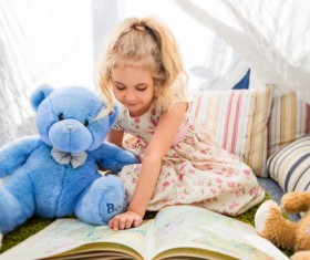 And teddy bears little girl reading a book together Stock Photo
