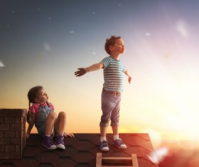 Climb the little boy on the roof with the little girl Stock Photo