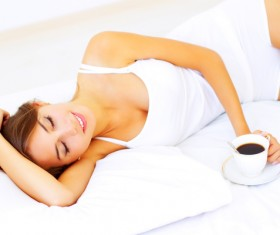Girl lying in bed drinking coffee Stock Photo 01