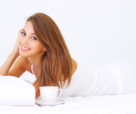 Girl lying in bed drinking coffee Stock Photo 02