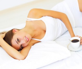 Girl lying in bed drinking coffee Stock Photo 03