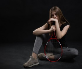 Girl sitting on the floor holding a tennis racket HD picture