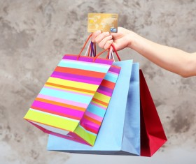 Holding a shopping bag with a bank card for a woman Stock Photo 01