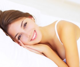 Smiling girl lying on the bed Stock Photo 01