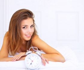 Smiling girl with alarm clock Stock Photo