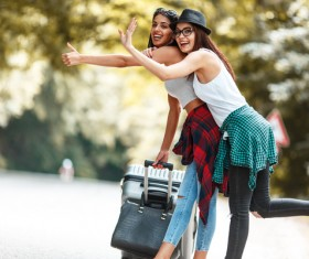 Two women who dragged the suitcase wanted a free ride Stock Photo