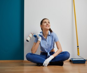 Woman holding a roller brush in front of a white wall resting Stock Photo