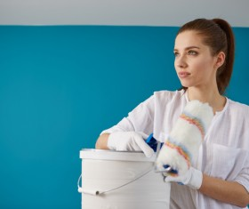 woman who holds a roller brush and a paint bucket Stock Photo