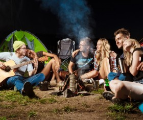 Camping friends sitting around the campfire to play guitar Stock Photo