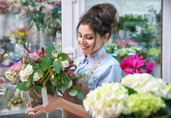 Beautiful Woman Florist Holding Pot With Flowers In Flower