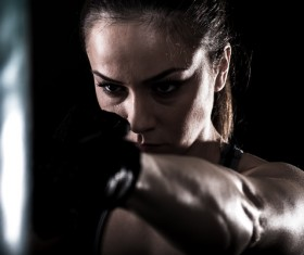 Hitting sandbags female boxer Stock Photo