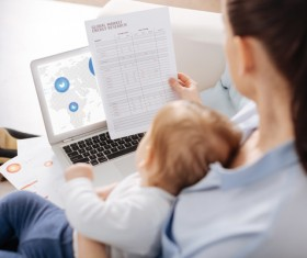 Holding the baby's mother looking at the business report HD picture