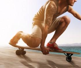 Kneeling skateboarding youth Stock Photo