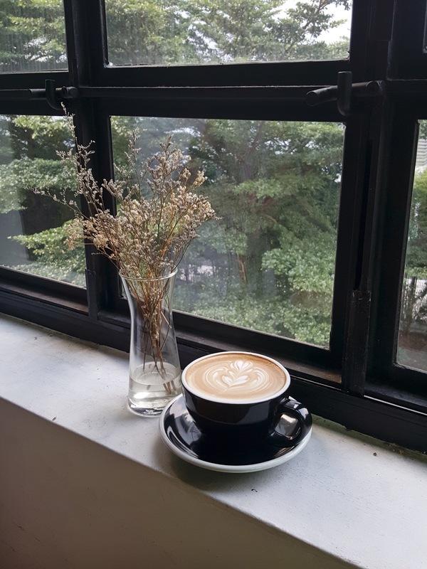 Latte coffee and bottles on the windowsill flower Stock Photo